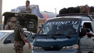 Beväpnade män vakar över irakier som flytt våldet i staden Mosul.