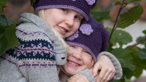 två blonda flickor iklädda tröjor och virkade mössor kramas och ser glada ut