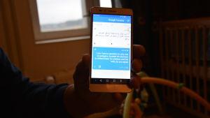 En hand håller upp en telefon där det först syns en text på arabiska och under den en dålig översättning på engelska som ställer frågan om det är rätt att en person kan bestämma att man ska skilja åt en man från hans fru och barn. I bakgrunden syns en spj