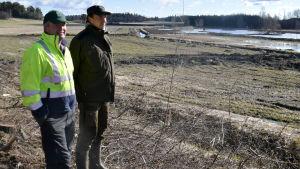 Anders Wasström och Ville Wahteristo står på en åker och blickar ut över en våtmark i Snappertuna.