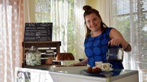 Emilia Nyberg står och häller kaffe i två kaffekoppar. På disken står flera fat med kakor och andra bakverk.