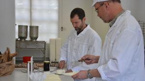 Thierry Jung och Hannu Nikander skär upp ost.