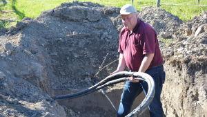 Stefan Juslenius håller i elkablen som grävts ner på hans gård i Mjölbolsta.