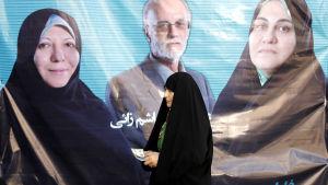 En kvinna går förbi valreklam i Teheran, Iran, den 24 februari 2016.