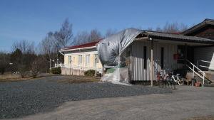 En presenning täcker gaveln av Kristinahemmet i Kristinestad efter att den gamla delen av byggnaden rivits ner.