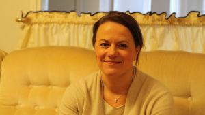 Laura Strömberg sitter på en soffa.