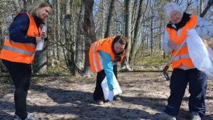 Mikaela Eriksson, Pamela Wikström och Eliina Rantakallio plockar skräp på Saro simstrand.