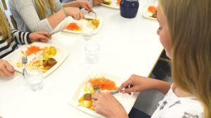 Elever som äter skolmat från engångstallrikar.