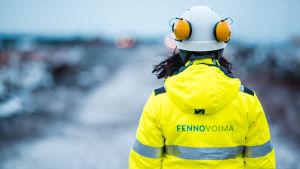 En kvinna i hjälm med texten Fennovoima på arbetsjackans rygg.