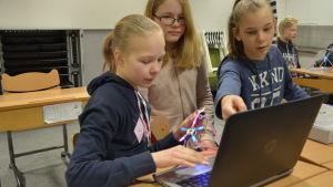 Tre flickor jobbar framför en dator.