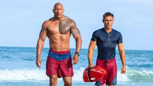 Mitch (Dawyne Johnson) och Matt (Zac Efron) går på stranden.