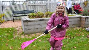 Flicka i rosa kläder krattar löv.