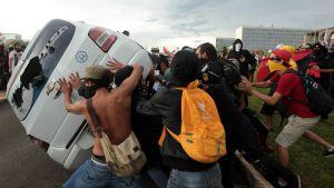 Demonstranter välter omkull en bil i Brasilia 29.11.2016