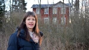Tove Söderholm framför den gamla, röda bondgården vid Wahlrooska hemmanet.