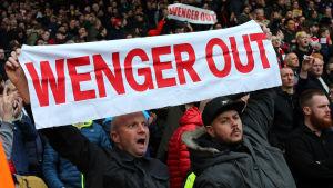 "En supporter håller upp ett plakat med texten ""Wenger out""."
