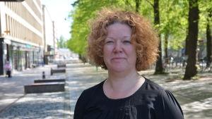 Maria Hällund står på gågatan i Vasa. Hon har rött, lockigt hår och en svart klänning på sig.