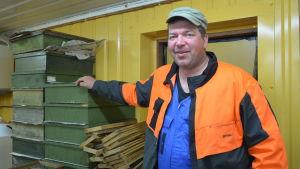 biodlaren christian storm står inomhus bredvid lådor till biodlingen