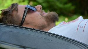 David Grönlund ligger i gräset. man ser hans ansikte ur fokus eftersom det i förgrunden ligger ett femtontums baselement. Elementet kräver 200 liter lådutrymme.