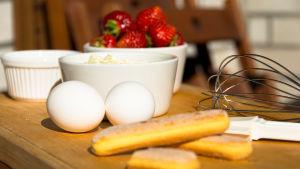 Efterrättsingredienser på ett skärbräde, jordgubbar, kex, ägg och mascarponeost.