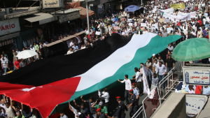 Jordanian demonstrators carry a giant Jordanian flag during an anti-government protest in Amman, Jordan, on 30 September 2011. According to media sources, thousands of Jordanians took to the streets in Amman and other major cities on 30 September demandin