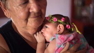 Ana Beatriz, en liten brasiliansk flicka som lider av mikrocefali med blomkrans på huvudet.
