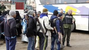 Rebeller i Homs köar med anhöriga inför bussresan norrut provinshuvudstaden Homs. Ryska och syriska poliser övervakade evakueringen tillsammans med Röda halvmånen