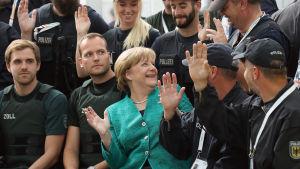 Angela Merkel sitter bland poliser.