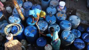 Kvinnor i Indien fyller på sina kanistrar med vatten