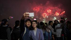 En kvinna och en man tar en selfie med Hongkongs hjärtformade fyrverkerier i bakgrunden.