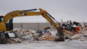 Grävmaskin och hög av avfall