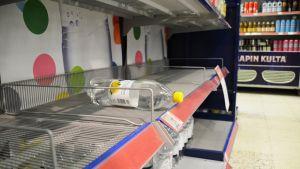 En ensam vattnflaska på en tom butikshylla.