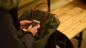 person med mobiltelefon och ryggsäck i knät