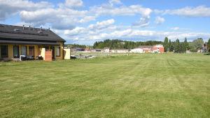 Radhuslängor på en stor gräsmatta som kallas Sjundeås hjärta.