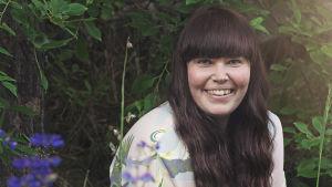 Närbild på en kvinna med långt brunt hår. I förgrunden syns blå sommarblommor.
