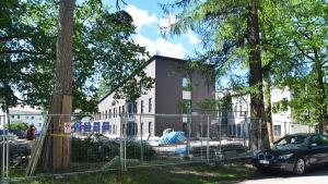 Ett hus i modern arkitektur och i en brungrå nyans som håller på att byggas. Runtom bygget går ett staket i metall och träd står inne på gården.