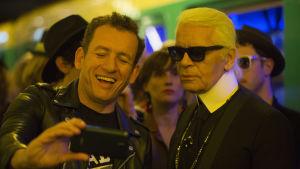 Jean-Rene (Dany Boon) tar en selfie tillsammans med Karl Lagerfeld.