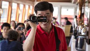 kiinalaisia turisteja lounaalla Finlandia Princessalla, kiinalaismies kuvaa handycam videokameralla