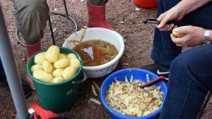 Några mänskor sitter och skalar potatis. På marken syns två handfat med potatisskal och ett ämbar med färdigskalad potatis.