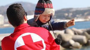 Röda Korset-medarbetare hjälper en flyktingpojke som anlänt till Kreta i Grekland.