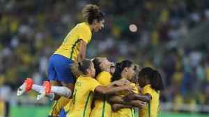 Brasiliens damlandslag i fotboll firar ett mål mot Sverige tillsammans.