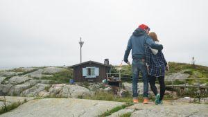 Adrian och Ylva Perera på Klovharun, stugan i bakgrunden.