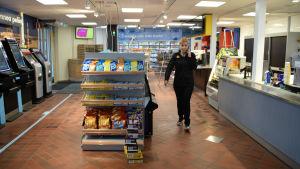 En kvinna talar i telefon inne i en Shell-bensinstation.