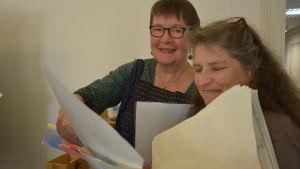 Två kvinnor bläddrar bland teckningar.