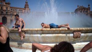 Människor svalkar sig i fontän i Sevilla, Spanien.