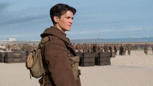 Tommy /Fionn Whitehead) står på stranden och i bakgrunden syns en massa andra soldater.