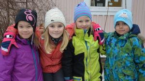 Fyra barn med armarna om varandra utomhus.