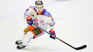 Vitklädd Henrik Haapala med guldhjälm på huvudet gör en sväng på isen.