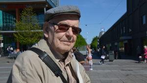 Valter Nyman sitter på en bänk i solskenet. Han har en keps på sig och mörka glasögon.