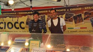 chokladförsäljarna stefano milan och mohamed chine står bakom sitt stånd med produkter runtom sig