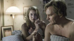 Äkta paret Anna och Erik röker i sängen.
